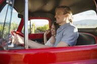 Affectionate smiling couple riding in truck in vineyard - HEROF03726