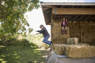 Brother and sister jumping and playing on hay bales in barn - HEROF03732