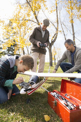 Boy fixing model airplane with father and grandfather in park - HEROF03759
