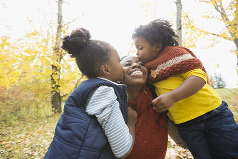 Affectionate daughters kissing mother in autumn woods - HEROF03768