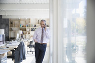 Businessman talking on cell phone at window in office - HEROF03816
