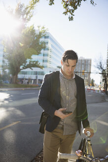 Businessman texting with cell phone commuting with bicycle on urban sidewalk - HEROF03837