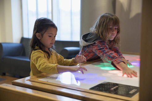 Boy and girl playing with touch screen light display in science center - HEROF03846