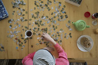 Young woman assembling jigsaw puzzle and drinking coffee at table - HEROF03864