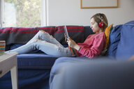 Young woman with headphones using digital tablet listening to music on sofa - HEROF03870