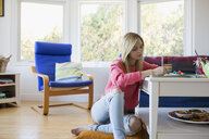 Young woman writing in notebook on coffee table - HEROF03873