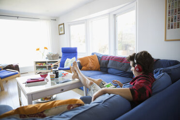 Young man with headphones using digital tablet on living room sofa - HEROF03879
