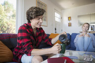 Young couple pouring and drinking coffee in living room - HEROF03882