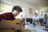 Young man playing guitar hanging out with friends in living room - HEROF03894