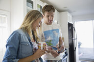 Young couple texting with cell phone drinking coffee in kitchen - HEROF03900