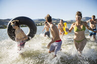 Young friends running and splashing in sunny summer lake - HEROF03912