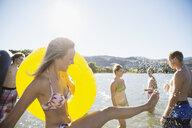 Young woman in bikini with inner tube splashing in summer sunny lake - HEROF03915