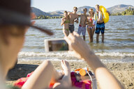Young woman with camera phone photographing friends at sunny summer lake - HEROF03918