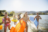 Young friends with inner tubes and inflatable rafts running in sunny summer lake - HEROF03921