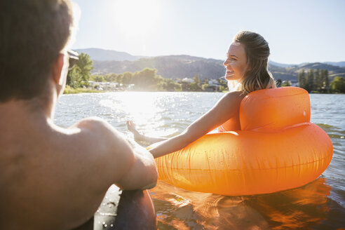 Young couple holding hands in inflatable rafts on sunny summer lake - HEROF03930