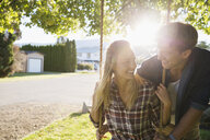 Young couple on swing in sunny summer yard - HEROF03936