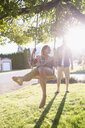 Young couple swinging at tree swing in sunny summer yard - HEROF03939
