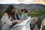 Women friends looking at map on automobile hood in vineyard - HEROF04032