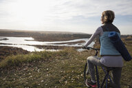 Woman with yoga mat on bicycle looking at autumn lake view - HEROF04080