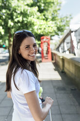 UK, London, portrait of smiling young woman on the street - MGOF03903