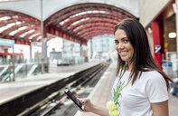 UK, London, portrait of smiling young woman holding cell phone in a train station - MGOF03915