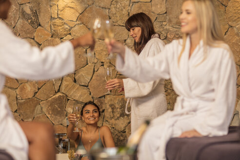 Happy women having a glass of champagne in a spa - ZEF16104
