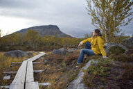 Finland, Lappland, Kilpisjaervi, woman sitting at wooden boardwalk - PSIF00200