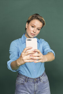Portrait of young woman taking selfie with smartphone in front of green background - VGF00149
