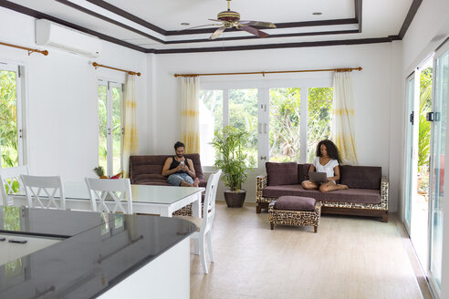 Thailand, couple sitting in spacious living room at holiday resort using electronic devices - MOMF00579