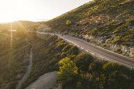 Italy, Elba Island, biker on coastal road against the sun, aerial view with drone - FBAF00217