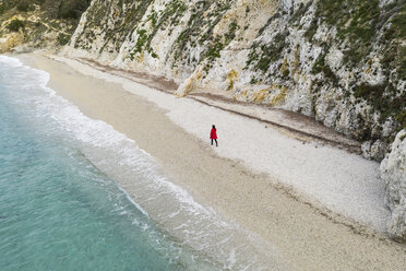 Italy, Elba, woman with red coat walking at beach, aerial view with drone - FBAF00220