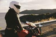 Italy, Elba Island, female motorcyclist at viewpoint - FBAF00229