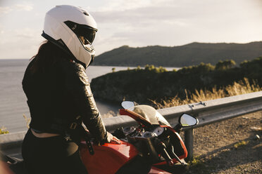 Italy, Elba Island, female motorcyclist at viewpoint - FBAF00229