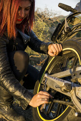 Red-haired woman repairing motorbike - FBAF00232