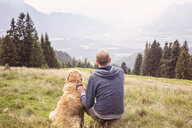 Austria, Tyrol, Kaiser mountains, man with dog on a hiking trip in the mountains - MAMF00280