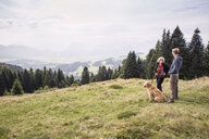 Austria, Tyrol, Kaiser mountains, mother and adult son with dog on a hiking trip in the mountains - MAMF00283