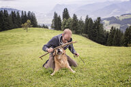 Austria, Tyrol, Kaiser mountains, man playing with dog on alpine meadow - MAMF00286