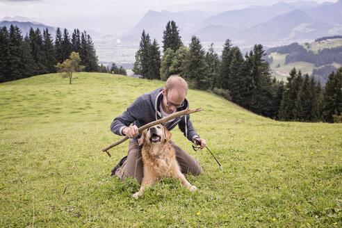 Austria, Tyrol, Kaiser mountains, man playing with dog on alpine meadow - MAMF00286