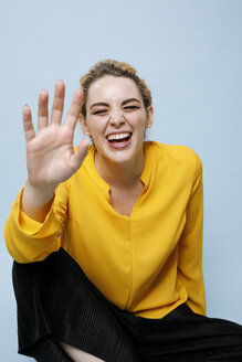 Portrait of laughing young woman wearing yellow blouse in front of blue background - GRSF00046
