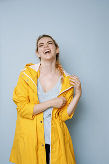 Portrait of laughing young woman wearing yellow rain coat in front of blue background - GRSF00049