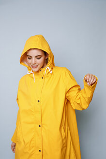Smiling young woman wearing yellow rain coat in front of blue background dancing - GRSF00052