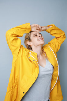Happy young woman wearing yellow rain coat in front of blue background - GRSF00055