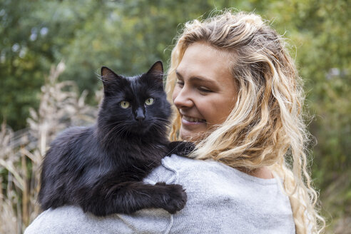 Portrait of black cat on shoulder of smiling young woman - TCF06064