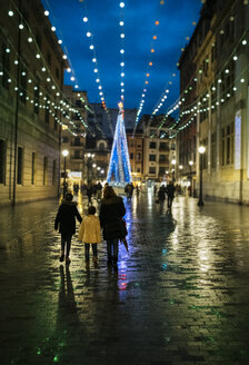 Spain, Gijon, back view of mother and two children walking at pedestrian area in the evening at Christmas time - MGOF03923