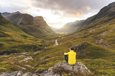 UK, Scotland, Man looking at view with the Three Sisters of Glencoe mountains on the left and the A82 road in the middle of the valley - WPEF01229