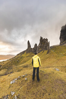 UK, Scotland, Isle of Skye, man hiking to The Old Man of Storr on a cloudy day - WPEF01232