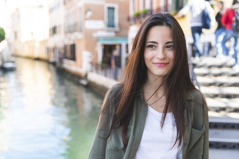 Italy, Venice, portrait of smiling young woman in the city with canal in background - WPEF01238