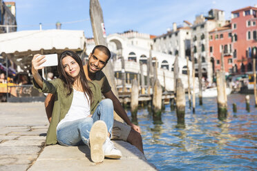 Italy, Venice, couple relaxing and taking a selfie with Rialto bridge in background - WPEF01241