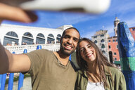 Italy, Venice, couple enjoying the city and taking a selfie with Rialto bridge in background - WPEF01244