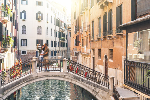 Italy, Venice, young couple standing on a small bridge taking a selfie - WPEF01247